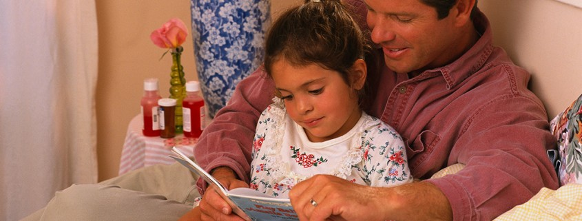 father reads to daughter in bed