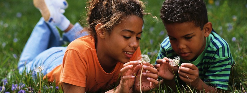 boy and girl play with dandelions