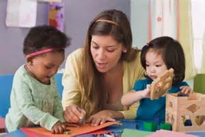 adult with young children playing and drawing
