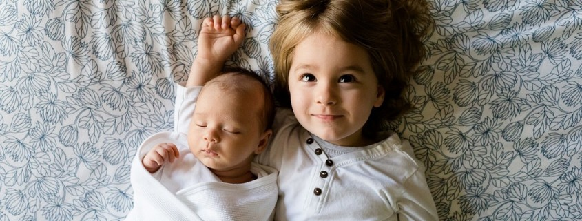 very young boy and babay laying on a bed