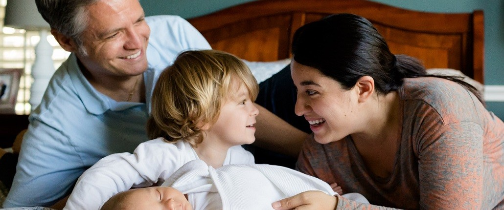 young family sharing a laugh on a bed