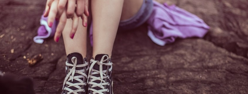 a child's legs and tennis shoes