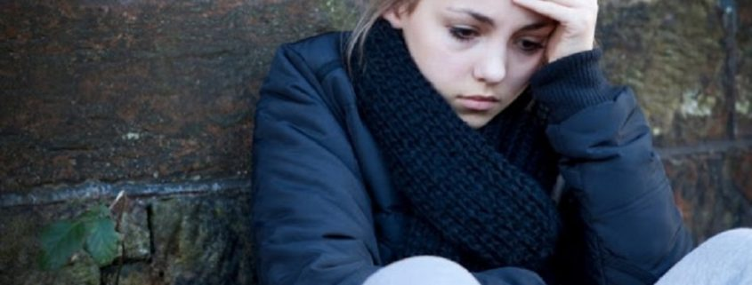 upset teenage girl sitting outside in the cold