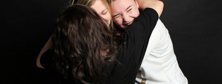 three girlfriends hugging