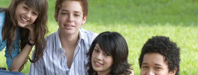 pre-teens sitting on grass