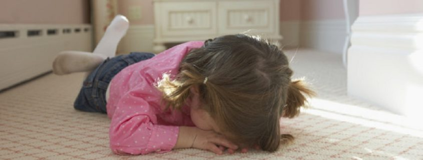 Young girl laying on bedroom carpet covering face